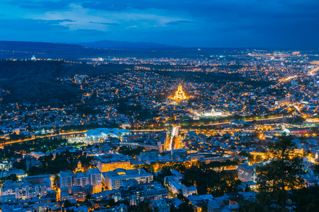 uptown: Tbilisi, Georgia. Aerial Cityscape View Of Capital In Evening Illimination, Modern Uptown, Baratashvili Bridge, Sameba Holy Trinity Cathedral. Dramatic Blue Cloudy Sky Of Sunset Over Hilly Area.