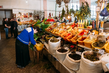 Batumi, Georgia - May 28, 2016: Side View Of Elderly Georgian Woman Dealer Sorting Fresh Greenery Near The Abundant Counter Of Fragrant Spices, Herbs, Sauces, Condiments At Covered Market, Bazar.