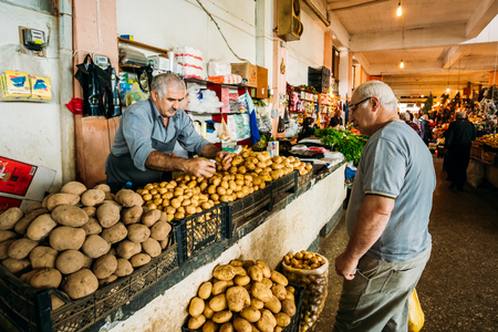 Batumi, Georgia - May 28, 2016: Side View Of Two Mature Georgian Men, The Buyer And Dealer Selling The Potato Of A New Crop At The Market Bazaar.