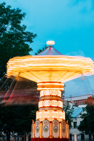 Blurred Motion Effect Around Of Brightly Illuminated Rotating High Speed Carousel Merry-Go-Round. Summer Evening In City Amusement Park. Stock Photo