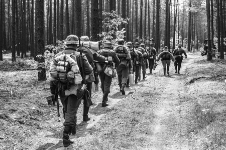 world war ii: Unidentified Re-enactors Dressed As World War II German Soldiers Walks On Forest Road. Black And White Photography