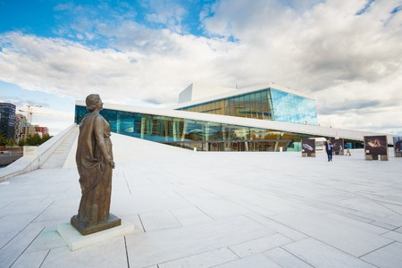 Oslo, Norway - July 31, 2014: Side View Of Glass Facade Of Oslo Opera And Ballet House. The Bronze Statue On White Marble Granite Floor Surface Under Cloudy Summer Sky. Editorial