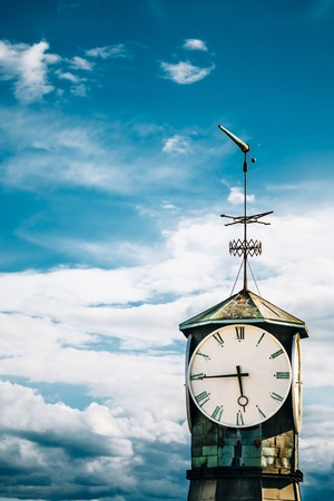 reference point: Oslo, Norway. Close View Of Top Part With Big Clock And Steeple Of Old Lighthouse At Aker Brygge District. Dramatic Blue Cloudy Sky Background