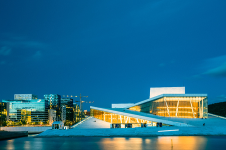 Oslo, Norway - July 31, 2014: The Scenic Night Evening View Of Illuminated Norwegian National Opera And Ballet House Among Contemporary High-Rise Buildings. Blue Sky Background, Copyspace. Editorial