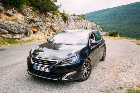 Verdon, France - June 29, 2015: Black colour Peugeot 308 5-door car on background of French mountain nature landscape. The Peugeot 308 is a small family car produced by French car manufacturer Peugeot Editorial