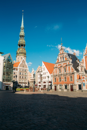 St. Peters Church And House Of The Blackheads In Riga, Latvia. Sunny Summer Day With Blue Sky. Famous Landmark. Old Architecture. Travel Destination. Nobody. Town Hall Square Stock Photo