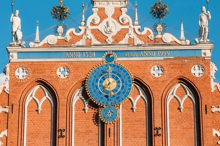 Sculptures On The Facade Of  The House Of Blackheads In Riga, Latvia. Famous Landmark. Travel Destination. Town Hall Square. Four Statues Named After Neptune, Agreement, Peace, Mercury. Astronomical Clock and emblems Stock Photo