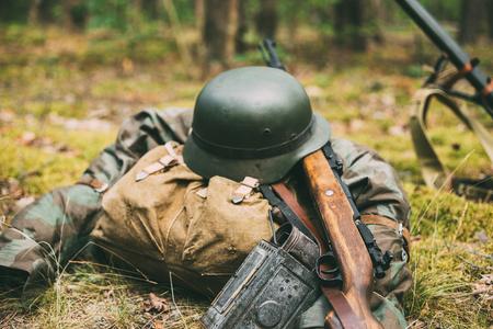 Duitse militaire munitie uit de Tweede Wereldoorlog op de grond. Militaire helm, verlichting, Rifle