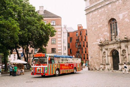 sightseeing tour: Riga, Latvia - July 1, 2016: The Colorful Striped Touristic Bus In The Historic Center Of Old Town, Going To Start For Panorama City Sightseeing Tour. Editorial