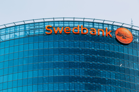 headquarter: Riga, Latvia - June 30, 2016: Close View Of Blue Glass Building Facade Of Headquarter Of Swedbank With Red Signboard And Round Logotype On It. Editorial