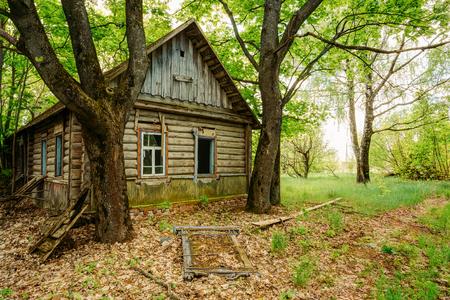 Die Verlassene Holz Land Blockhaus unter grünen Bäumen, Verlassene Nach Tschernobyl-Katastrophe vor etwa 30 Jahren. Ausschluss nach der Durchführung der radioaktiven Verseuchung in der Sommer-Frühling.