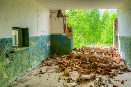 exclusion: Destroyed Abandoned Rural Shop With Ruined Brick Wall In Nuclear Contamination Zone After Chernobyl Catastrophe. Exclusion Area With Opulent Vegetation In Summer Spring Sunny Day Stock Photo