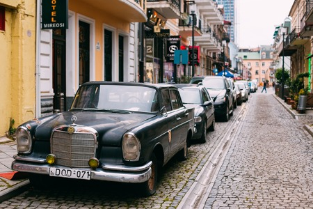the outmoded: Batumi, Georgia - May 28, 2016: The Black Rarity Retro Mercedes Benz Car Parked On The Narrow Paved Street In A Row With Another Modern Automobiles In Summer Daytime.