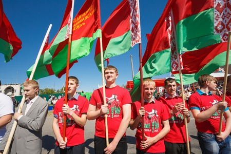 Gomel, Belarus - May 9, 2014: Unidentified youth from patriotic party BRSM holds flags on the celebration of Victory Day.