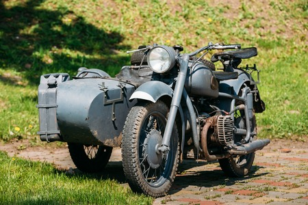 sidecar: The Old Rarity Tricar, Three-Wheeled Gray Motorcycle With A Sidecar Of German Forces Of World War 2 Time Standing As An Exhibit In Summer Sunny Park. Stock Photo