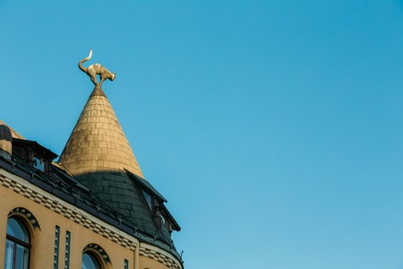 taper: Riga, Latvia. Sculpture Of Black Cat With Arched Back And Raised Tail On The Turret Taper Rooftop Of Cat House, Famous Landmark On Blue Sky Background.