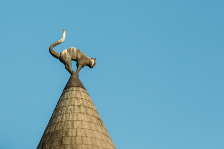 taper: Riga, Latvia. Close View Of The Sculpture Of Black Cat With Arched Back And Raised Tail On The Turret Taper Rooftop Of Cat House, Famous Landmark On Blue Sky Background.