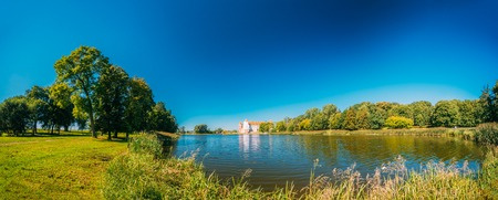 feudalism: Mir, Belarus. Panoramic View Of Mir Castle Complex From Side Of Lake. Architectural Ensemble Of Feudalism, Ancient Cultural Monument, Famous Landmark In Summer Sunny Day Under Blue Sky, Copyspace. Stock Photo