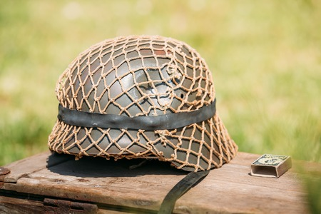 Close The Metal Helmet Of Infantry Soldier Of Wehrmacht, Armed Forces Of Nazi Germany During World War II, Lying On The Old Wooden Box On The Green Grass Background. Stock Photo