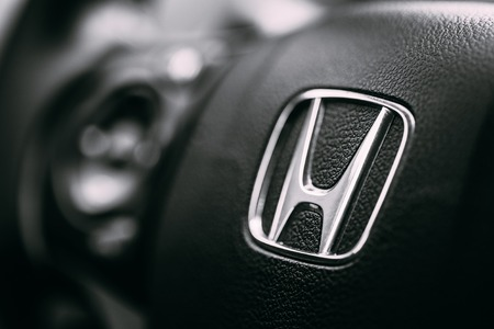 Borgund, Norway - August 1, 2014: Honda Black Steering Wheel And Silver Logo. Honda Motor Co., Ltd. is a Japanese public multinational conglomerate corporation. Editoriali