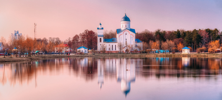 The View Of Alexander Nevsky Orthodox Christian Church With Bell Tower And Chapel On The Lake Shore In Sunset Sunrise Dawn, Early Spring, Forest Park Background. Gomel, Homiel, Belarus Stock Photo