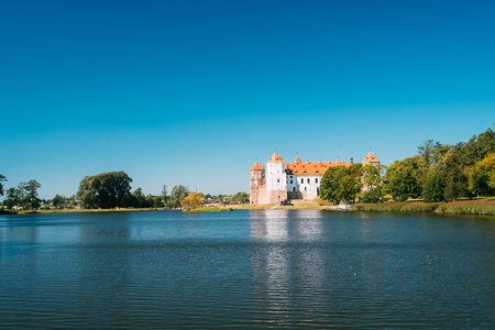 Mir, Belarus. Scenic View Of Mir Castle Complex From Side Of Lake. Architectural Ensemble Of Feudalism, Ancient Cultural Monument, Unesco Heritage. Famous Landmark In Summer Sunny Day Under Blue Sky