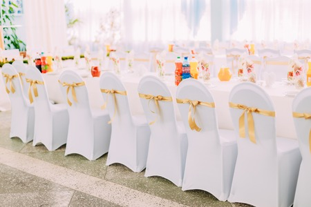 mantles: Decorative White Mantles And Colored Ribbons On Chairs At Festive Table. Chairs And Table Covered With Cloth. Stock Photo