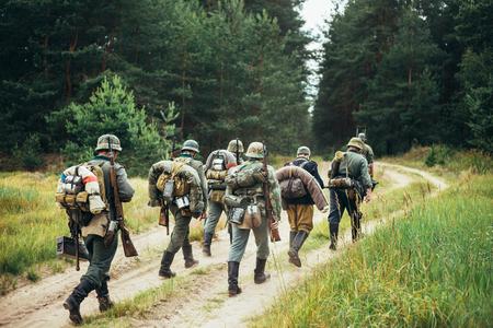reenactmant: Group Of Unidentified Re-enactors Dressed As German Soldiers Marching Along Forest Road. Summer Season.