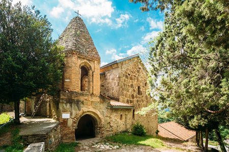 Mtskheta, Georgia. The Church Of St. John The Baptist, The Earliest Stone Building Of Shio-Mgvime Monastery, Medieval Monastic Complex With Carved Caves In Sunny Spring. Stock Photo