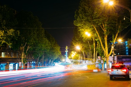 rustaveli: Tbilisi, Georgia - May 20, 2016: Night View Of The Liberty Monument And Rustaveli Avenue In Bright Illumination With White And Red Motion Blur Effect On The Road In Summer Under Black Sky.