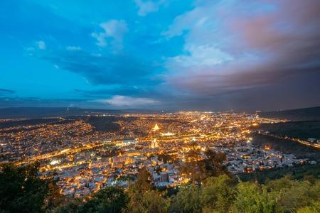 mauve: Tbilisi, Georgia. Picturesque Panoramic Aerial Cityscape In Bright Yellow Evening Illumination Under Dramatic Blue And Magenta Sky In Summer Twilight.