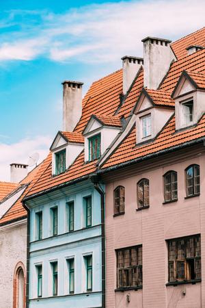 dormer: Riga Latvia. Mansard Tile Roof With Four Gable Fronted Dormer Windows On The Old Building Under Blue Sky