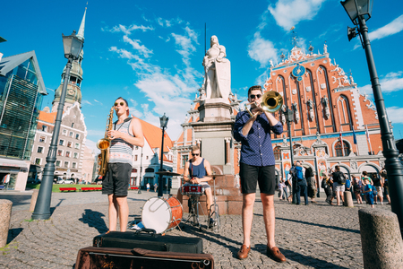 Riga, Latvia - July 1, 2016: Street Music Trio Band Of Three Young Musicians Guys Playing The Instruments For Donation On The Town Hall Square, Famous Touristic Showplace Of Old Town In Sunny Summer. Editorial