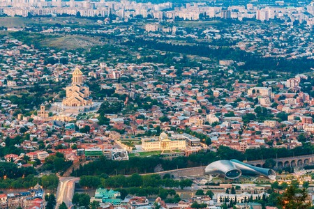 populous: Tbilisi, Georgia. Evening Aerial Panoramic View Of Sameba Complex, Holy Trinity Cathedral Surrounded By Populous Residential Area In Summer Dusk.