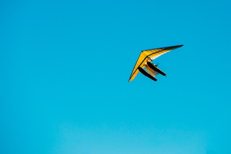 motorizado: Motorized Hang Glider Flying On Blue Clear Sunny Sky Background