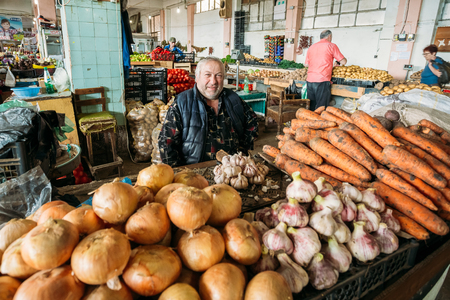 Mature Stocky Georgian Man Dealer Of Vegetables Is Sitting At Co