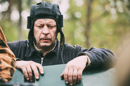 Portrait Of Unidentified Re-enactors Dressed As Russian Soviet Crew Member Soldier Of World War Ii Standing At Armoured Soviet Scout Car Ba-64 In Forest.