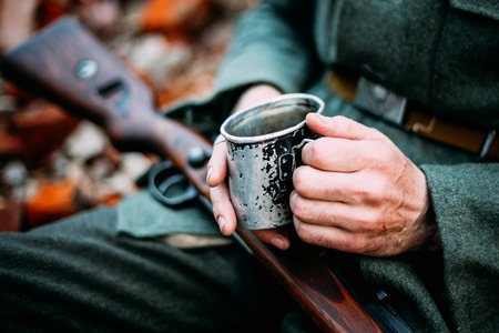 Unidentified Re-enactor Dressed As German Wehrmacht Infantry Soldier In World War II Holding Cup With Hot Water Or Tea In Camping In Autumn Forest. Stock Photo