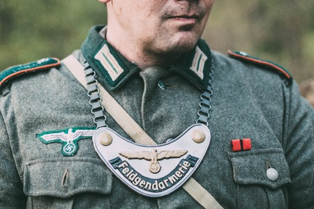 reenactmant: Close Up Unidentified Re-enactor Dressed As German Wehrmacht Soldier Feldgendarm In World War II With Gorget. The Inscription On Gorget , Field Gendarmerie. Military Police