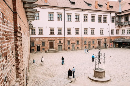 Mir, Belarus. People Walking In Courtyard Of Castle. Architectural Ensemble Of Feudalism, Ancient Cultural Monument, UNESCO Heritage. Famous Landmark