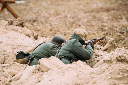 reenactmant: Two Unidentified Re-enactors Dressed As German Wehrmacht Infantry Soldiers In World War II Hidden Sitting With Rifle Weapon In An Ambush In Trench In Autumn Field