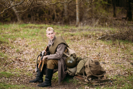 reenaction: Pribor, Belarus - April 23, 2016: Young Man Re-enactor Dressed As Russian Soviet Red Army Infantry Soldier Of World War II Sit Near Military Equipment With Mosin-Nagant Rifle In Hands In Forest