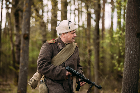 Pribor, Belarus - April 23, 2016: Man Re-enactor Dressed As Russian Soviet Red Army Infantry Soldier Of World War II Walking With PPS Submachine Gun In Hands In Forest