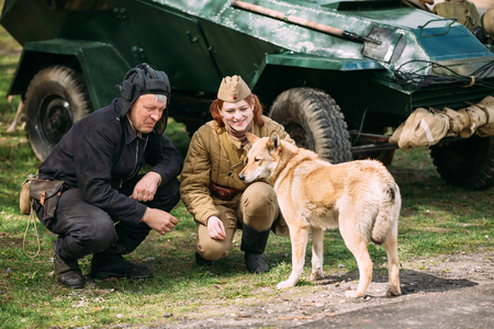 reenaction: Pribor, Belarus - April 23, 2016: Young Woman And Man Re-enactors Dressed As Russian Soviet Red Army Soldiers Of World War II Playing with Dog