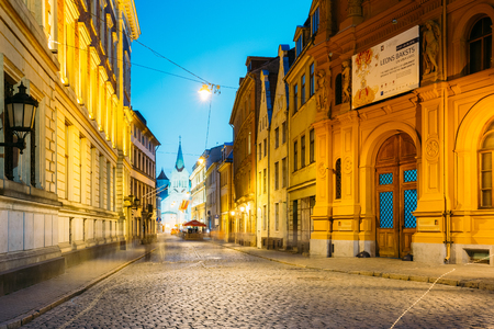 Riga, Latvia - July 1, 2016: Evening View Of Pils Street With Ancient Architecture In Bright Warm Yellow Illumination Under Summer Blue Sky. Our Lady Of Sorrows Or Virgin Of Anguish Church In Distance Editorial