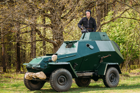 Pribor, Belarus - April 23, 2016: Re-enactor Dressed As Russian Soviet Crew Member Soldier Of World War II Sitting In Armoured Soviet Scout Car BA-64 In Forest.