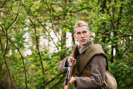 Pribor, Belarus - April 23, 2016: Potrait Of Young Re-enactor Dressed As Russian Soviet Infantry Red Army Soldier Of World War II Aiming a Mosin-Nagant Rifle Weapon at Enemy