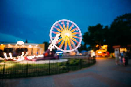 Abstract Blur Image Of Illuminated Ferris Wheel In Amusement Park