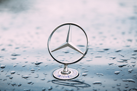 Close View Of Metal Star Logo Of Mercedes Benz At Wet Hood Of Blue Editorial