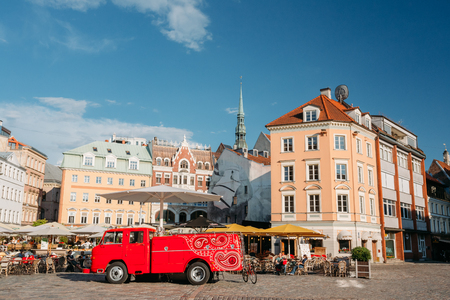 Riga, Latvia. Big Red Car Of Street Musicians Buskers Stands Near